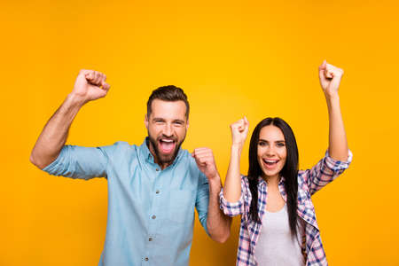 Portrait of joyful lucky couple with raised arms celebrating victory of football team yelling loudly isolated on vivid yellow background