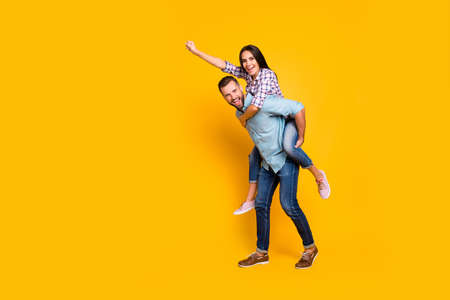 Full size portrait of playful carefree couple in piggy back style making super man sign with raised fist isolated on bright yellow background