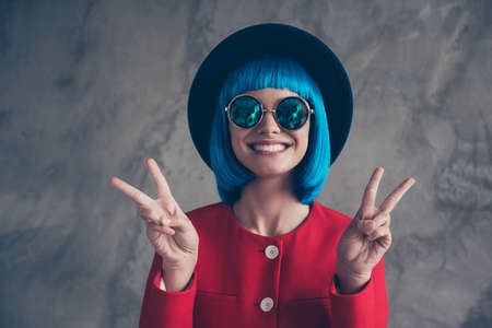 Portrait of funny peaceful girl in eyewear headwear blue wig with beaming toothy smile gesturing v-signs with two hands isolated on grey background