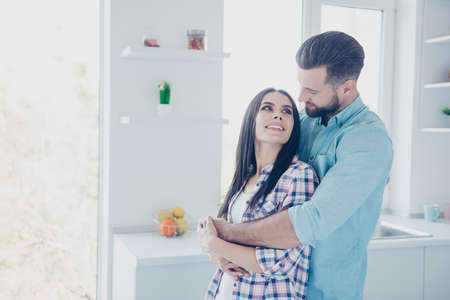 Portrait of coquettish couple, handsome man hugging charming woman enjoying free time together in modern white kitchen. True feelings honeymoon delight concept Banque d'images - 105912954