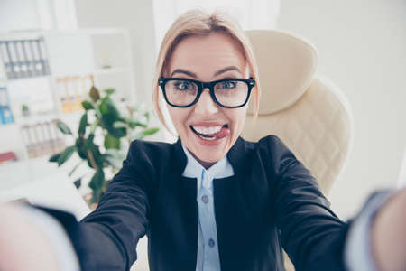 Self portrait of playful funny woman in eyeglasses shooting selfie on front camera gesturing tongue out having online meeting sitting in modern workplace Stock Photo