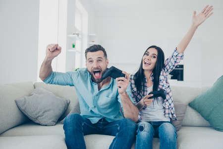 ビデオゲームで勝利を楽しむポジティブな陽気な配偶者の肖像画は、屋内のソファに座って叫ぶ叫び声を上げて拳を上げました。エンターテイメント運成功目標達成コンセプト
