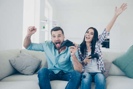 Portrait of positive cheerful spouses enjoying victory in video game holding raised fists shouting screaming sitting on sofa indoor. Entertainment luck success target goal achievement concept