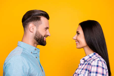 Profile portrait of cheerful joyful couple standing face to face wearing shirts isolated on vivid yellow background