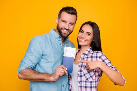 Portret van blij blij paar bedrijf paspoort met vliegende kaartjes in handen wijzend met wijsvinger kijken camera geïsoleerd op heldere gele achtergrond