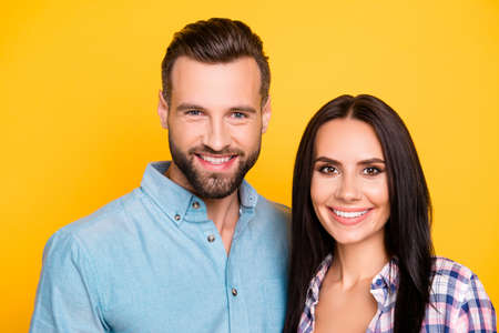 Head shot portrait of trendy attractive couple with beaming white smiles isolated on bright yellow background. Love story true feelings concept
