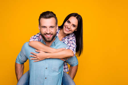 Portrait with copy space of lovely romantic couple, handsome man carrying on back charming woman looking at camera isolated on vivid yellow background