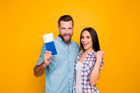 Portrait of successful lucky couple getting visa abroad holding raised fist showing passport with flying tickets shouting with wide open mouth isolated on vivid yellow background Stockfoto
