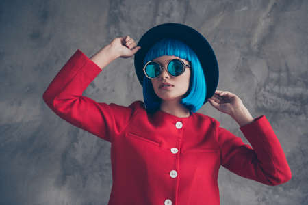 Portrait of stunning gorgeous girl in eyeglasses red jacket holding two hands on hat isolated on grey background. Modern image seasonal trend concept Stok Fotoğraf