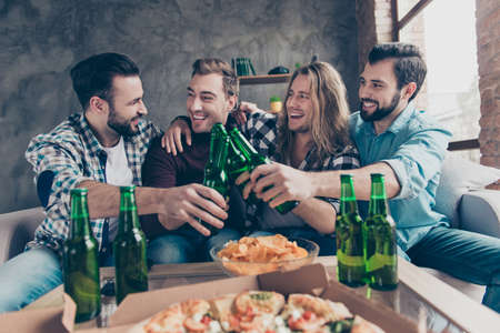 Stylish, bearded, successful guy said funny toast, his stylish friends with modern hairstyle looking at him and laughing, team of four persons clinking bottles with lager, having snacks on the table