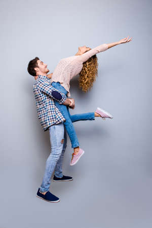 I believe I can fly! Side view full body portrait of cool fit couple in jeans sneakers making denim outfits dancing stunt isolated on grey background Stock Photo