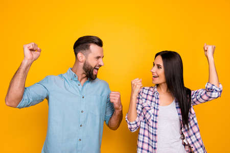 Portrait of joyful successful couple with raised arms looking at each other yelling celebrating achievement isolated on bright yellow background
