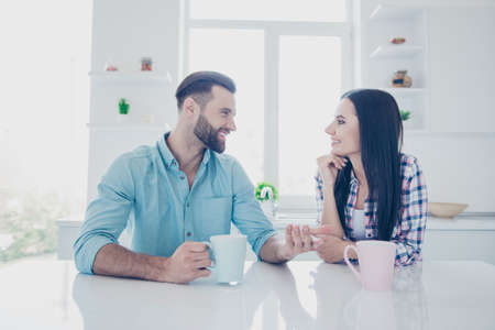 Portrait of positive couple sitting in modern white kitchen drinking tea sharing gossips news gesturing with hand enjoying morning together