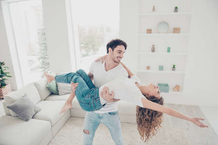 Portrait of stylish trendy partners enjoying weekend together indoor wearing white t-shirts jeans standing in modern livingroom. Happiness delight pleasure home party concept