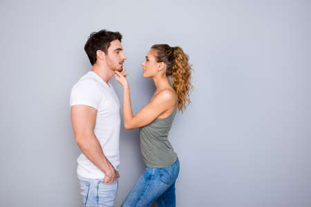 Understanding trust support concept. Profile portrait of attractive stylish couple, pretty charming woman touching muscular man face to face contact isolated on grey background