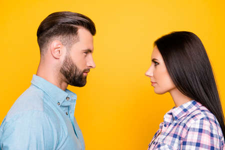 Profile portrait of jealous angry couple standing face to face having problem conflict isolated on vivid yellow background. Psychology concept