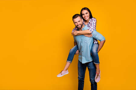 Advertisement concept. Portrait with copy space empty place of handsome man carrying on back pretty woman looking at camera isolated on vivid yellow background