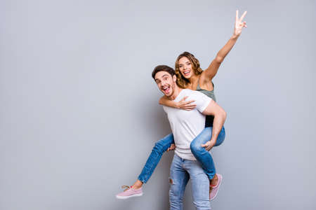 Hi! Portrait with copy space empty place of friendly peaceful couple, amazed man carrying on back charming woman gesturing v-sign isolated on grey background Banco de Imagens