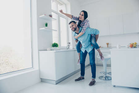 Full length portrait of funny comic couple, strong man carrying on back cheerful woman in piggy back style gesturing super man sign enjoying weekend together in modern white kitchen with interior