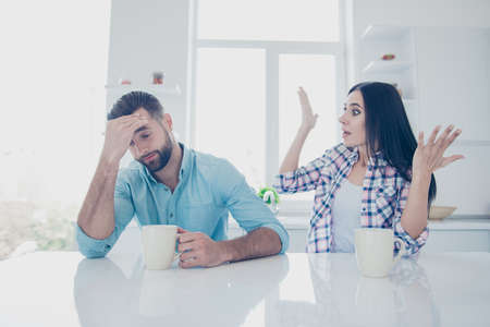 Portrait of shocked frustrated woman gesturing with hands shouting at unhappy upset man sitting in modern white kitchen. Scandal psychology negative distrust misunderstanding concept