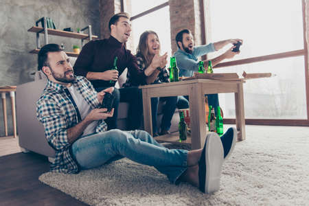 Bottom view of four attractive, stylish, successful players keen on video game, two persons holding joystick another cheering, support them, with impressed reaction sitting in living room