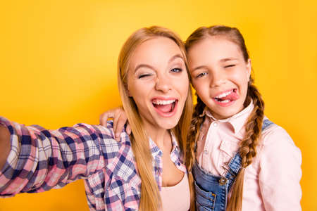 Close up photo picture portrait of candid careless pretty joyful funny funky cheerful glad hugging embracing girls making selfie isolated on bright background