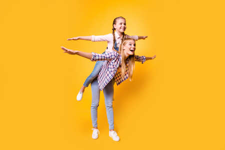 Friendship casual clothes older adult two different blonde haired concept. Full length body size view photo of funky rejoicing joyful sibling holding carrying sister on back isolated bright background