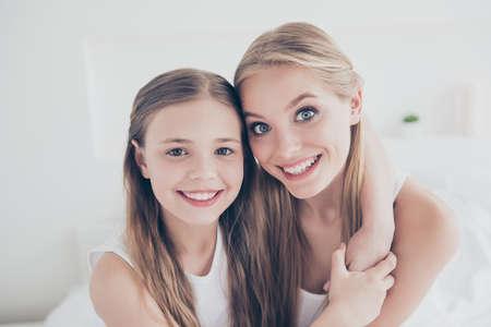 Cerrar retrato foto de familia de lindo dulce encantador hermoso encantador alegre alegre con gran sonrisa radiante mamá y su bonita hija abrazando el cuello pasar tiempo juntos la vida doméstica