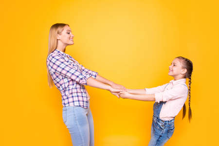 Whirl round freedom carefree weekend spend time together concept.  Portrait of two pretty joyful excited rejoicing cute sweet girls gripping palms looking at each other isolated on bright background Stock Photo