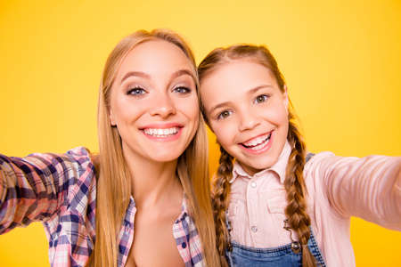 Close up photo portrait of candid careless funky funny pretty sweet laughing cheerful chilling out nice glad ladies taking selfie isolated on bright vivid background Stock Photo