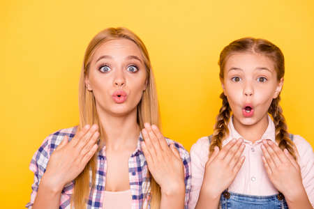 Close up portrait of two pretty lovely cute excited glad rejoicing impressed beautiful girls with blowing lips big eyes isolated on bright background