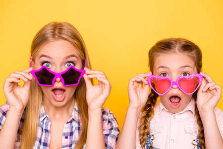 Close up portrait of cool dreamy friends joy concept. Close up portrait of different aged siblings with funky emotion expressing touching glasses isolated on bright background