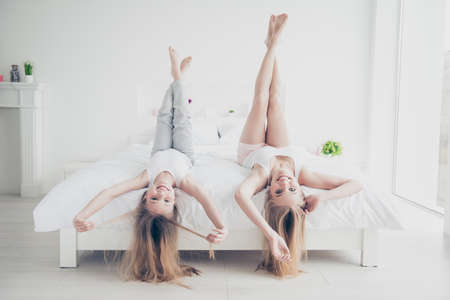 Adult mom mommy mum motherhood emotion expressing delight rejoice concept. Pretty funny laughing funky beautiful cute lovely girls lying upside down on bed touching long healthy hairstyle