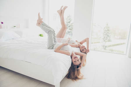 Freedom feeling facial emotion expressing concept. Pretty beautiful cute excited childish joyful lovely nice glad attractive wearing clothes for sleeping girls holding legs up lying on bed bare foot