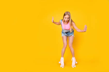 Portrait of shocked wondered girl learning roller skating keeping balance trying not to fall down isolated on yellow background, wellness activity workout fitness concept Imagens