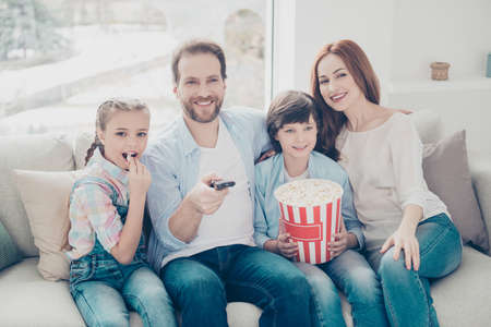 Portrait of joyful mama daddy two kids looking tv sitting on sofa having popcorn in hands using console searching favorite program enjoying comedy. Domestic lifestyle concept Stock Photo