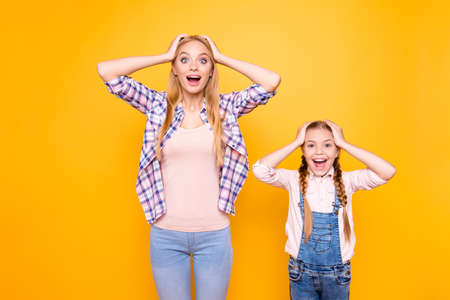 Portrait of crazy rejoicing delightful cute pretty girls wearing denim overalls touching heads isolated on bright background