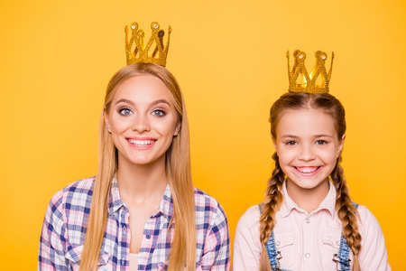 Older younger youth best favorite concept. Close up portrait of excited positive funny funky stylish joyful beautiful lady and cute sweet kid with pigtails with golden crown isolated bright background 写真素材