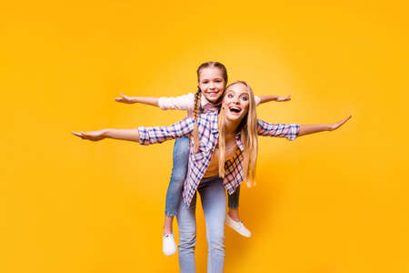 Parenthood siblings game checkered shirt stylish modern outfit concept. Excited cheerful cute funky carefree pretty mum carrying on back kid making airplane winds isolated on bright background Stock Photo