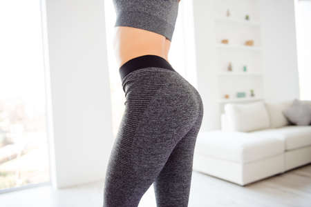 Weightloss wellness eating nutrition vitality concept. Cropped close up view photo of sexual sporty sportive tempting beautiful attractive nice round ass wearing gray tight pants leggings Foto de archivo
