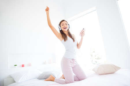 Portrait of cheerful positive girl dancing on bed using smart phone and headset listening favorite music enjoying morning time