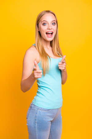 Vertical photo of happy young blond woman stand against yellow background and giving thumbs up success hand sign. I choose you! Girl with toothy beaming smile and wide open eyes look at camera