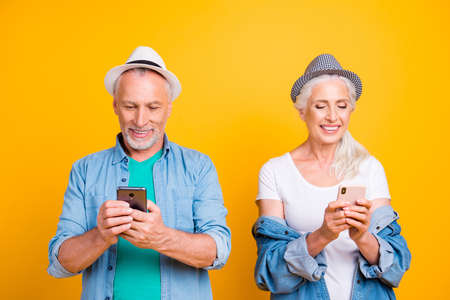 Cellular texting read news media browsing concept. Close up photo portrait of excited pretty cheerful nice glad careless partners using holding telephones in hands isolated on bright background