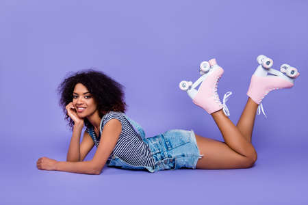 Portrait of stylish trendy girl lying on stomach demonstrate pink roller skates on legs having free time pause isolated on bright violent background retro vintage quad student concept