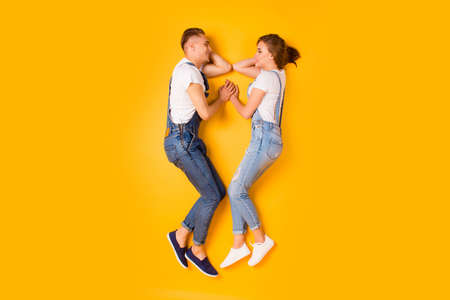 Feelings legs shoes sneakers concept. Full length high angle size photo portrait of two stylish cute lovely in denim outfit spouses enjoying life looking at each other isolated on bright background 스톡 콘텐츠