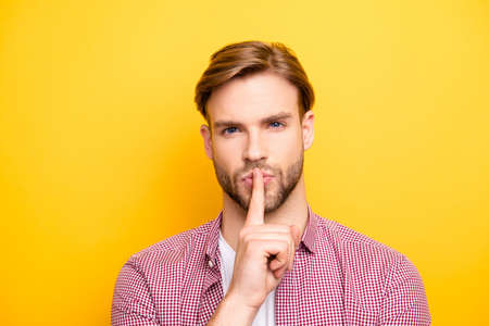 Close up portrait of confident pensive dreamy handsome sexy guy with stylish modern hairdo holding forefinger near mouth asking to be quiet isolated on bright yellow background copy-space Stock Photo