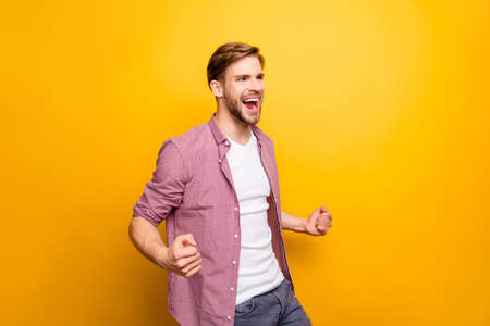 Lifestyle leisure people rejoice delightful carefree people person concept. Half-turned portrait of successful handsome motivated ambitious boy raising fists up isolated on bright background