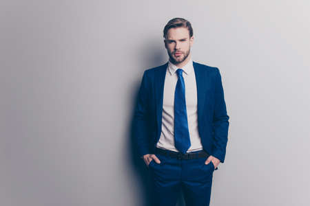 Portrait of stunning, attractive, sexy, brutal man in blue suit with tie with stubble, holding two hands in pockets of pants, looking ta camera, isolated on grey background 스톡 콘텐츠