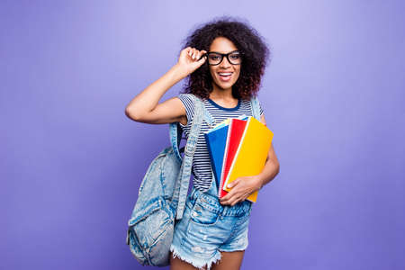 Portrait of cheerful positive girl in eyewear denim outfit shorts holding eyelet having colorful books looking at camera going for extra lessons isolated on violent background Stock Photo