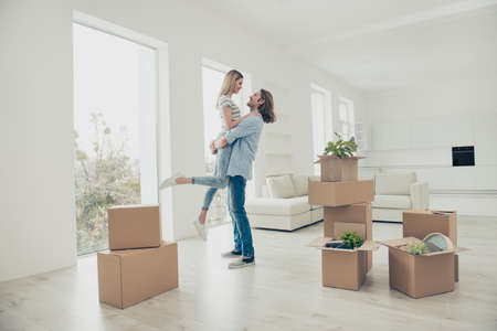 Out dreams come true! Lifestyle modern stylish dreamy trendy loft flat concept. Adorable beautiful attractive excited cheerful joyful couple dancing in new house